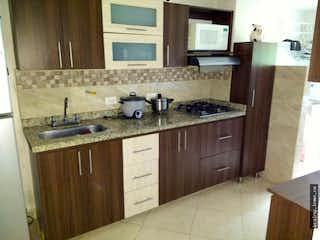 Una cocina con una estufa de fregadero y armarios en Apartamento en venta en San José, Envigado.