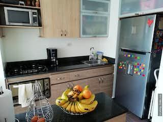 Una estufa encima del horno sentado al lado de un refrigerador en Apartamento en venta en Prados de Sabaneta.
