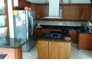 Una cocina con una estufa de nevera y fregadero en Casa en venta. Sabaneta. San Jose.