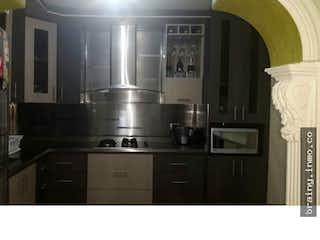 Una cocina en blanco y negro con electrodomésticos de acero inoxidable en Casa en venta. Itagui. Santa Maria.