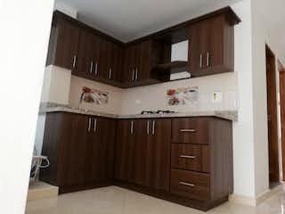 Una cocina con armarios de madera y un refrigerador blanco en Apartamento en venta en El Carmelo, Itagui.