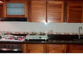 Una cocina con armarios de madera y un horno de cocina en Casa en venta en San Antonio de Prado.