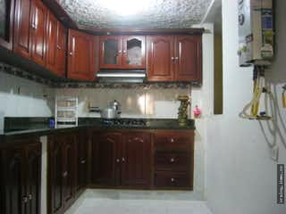 Una cocina con armarios de madera y electrodomésticos de acero inoxidable en Casa en venta en La Estrella.