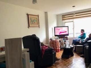 Un hombre sentado en un sofá frente a una televisión en Apartamento en Corferias, Quinta Paredes con 3 habitaciones - 118 mt2.