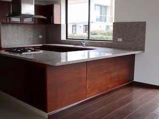 Una cocina con armarios de madera y un mostrador negro en Camino de los Cerezos