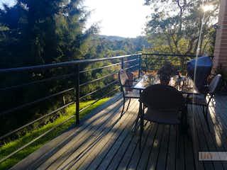 Un banco de madera sentado en una cubierta de madera en Casa en Alto de las Palmas, Envigado - 3500mt, tres alcobas, terraza