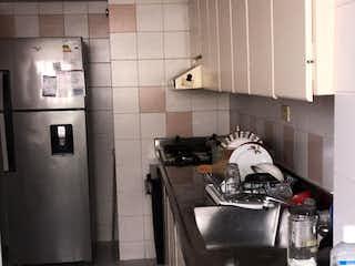 Una cocina con una estufa y un fregadero en Condominio los Duque