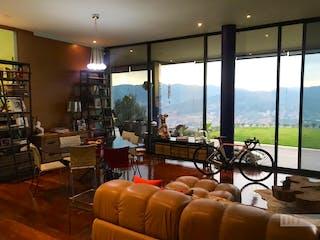 Una sala de estar llena de muebles y una gran ventana en Casa en Las Palmas, El Poblado con 3 habitaciones y parqueadero - 1583 mt2.