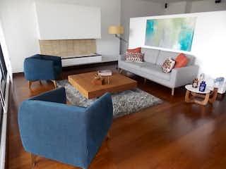 Una sala de estar llena de muebles y una televisión de pantalla plana en Apartamento de 245m2 en Cerros de Suba, Bogotá - con tres habitaciones