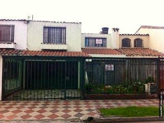 Un gran edificio de ladrillo con un banco en frente de él en Casa en venta en Barrio Modelia de 4 alcoba
