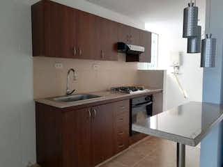 Una cocina con una estufa de fregadero y armarios en Apartamento en El Esmeraldal, Envigado -