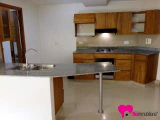 Una cocina con armarios de madera y una mesa de madera en Apartamento en Sabaneta, La Doctora - 109mt, tres alcobas, cuarto útil