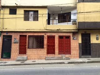 Un edificio de ladrillo rojo con una puerta roja en Casa en Venta LAS FLORES