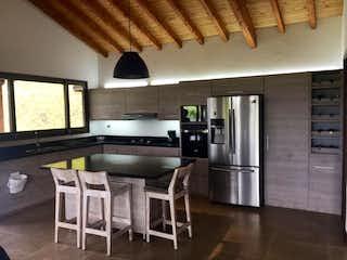 Una cocina con una mesa y una nevera en Casa en Venta CARMEN DE VIBORAL