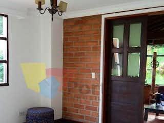 Una sala de estar con chimenea y una silla en Casa en Vereda Las Lomitas-Sabaneta, con 4 Habitaciones - 280 mt2.