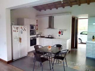 Una cocina con una mesa y una nevera en Casa En La Loma del Escobero - Envigado, con tres habitaciones