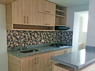 Una cocina con una estufa de fregadero y armarios en Puerto Nuevo