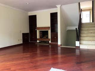 Una sala de estar con suelos de madera dura y una chimenea en Casa