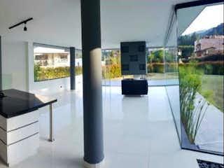 Una gran habitación blanca con una gran ventana en Casa En La Loma de Escobero - Envigado, con dos niveles