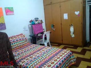 Un dormitorio con una cama y un televisor en -
