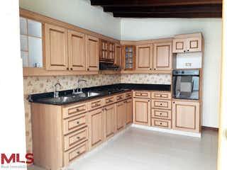 Una cocina con armarios blancos y electrodomésticos negros en No aplica
