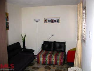 Una sala de estar con un sofá negro y una silla negra en -