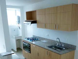Una cocina con un fregadero y un horno de cocina en -
