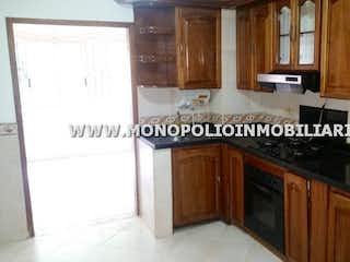 Una cocina con armarios de madera y un mostrador negro en CASA FINCA EN VENTA - TRES ESQUINAS SABANETA COD: 10885