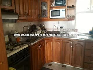Una cocina con armarios de madera y un horno de cocina en SENDEROS SAN JACINTO 241